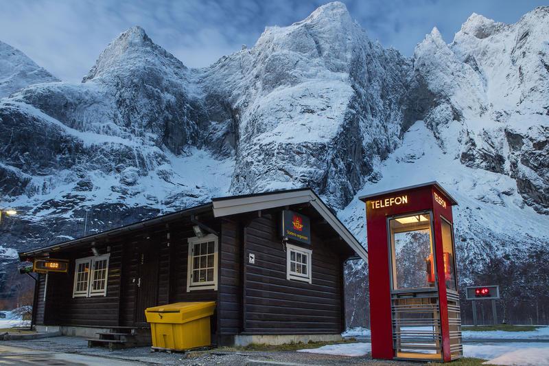 Rød telefonkiosk ved fjell og hus fra vegvesenet