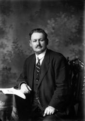 Ateljébild på en man i kostym, väst och slips med ett dokume