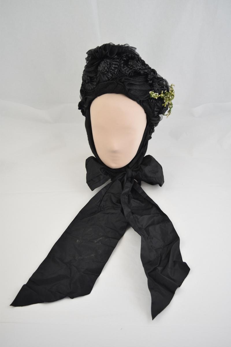 Sort strå. Stive bånd lagt på forskjellige måter dekker hele hatten. Den er pyntet med 11 sorte blomster i strå fra øre til øre, i nakken to sorte sløyfer, og grønn ranke med hvite små blomster slynger seg i S-form om pullen. To smale og to taftbånd 13 cm brede og 1 m lange, festet ved hvert øre. Sort silkefor.