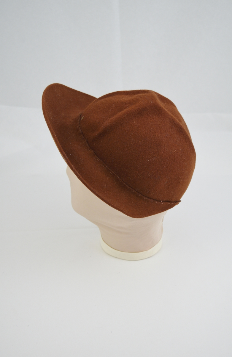 Form: kuleform. Bremmen er bred foran og slutter i to spisser ca. 8 cm fra hverandre bak. Tekstilbånd på innsiden langs bremmen, hvor en strikk er festet innunder. Ikke foret.