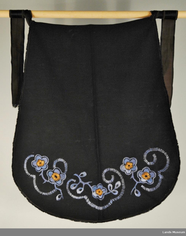 Svart forkle dekorert med blomster i plattsaum. Silkesatengsbånd til å knytte fast forkleet. Eit smalt frynset bånd rundt forkleet.