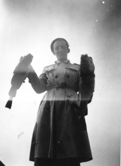 Fred Lundström håller upp två nyfångade fiskar. Lundström var ledsagare för konstnären Inge Schiöler på dennes permissioner från S:t Jörgens sjukhus