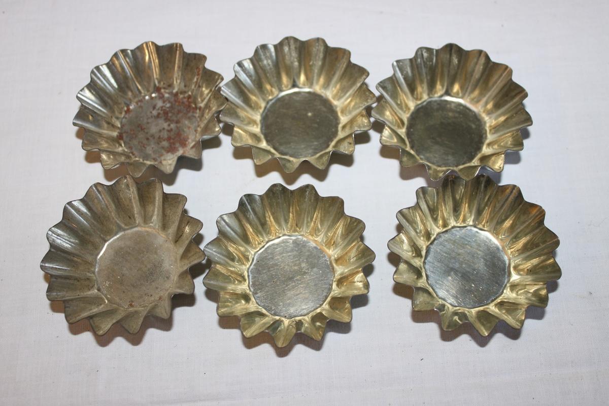 Sex stycken bakformar i formpressad plåt för mandelmusslor och liknande.