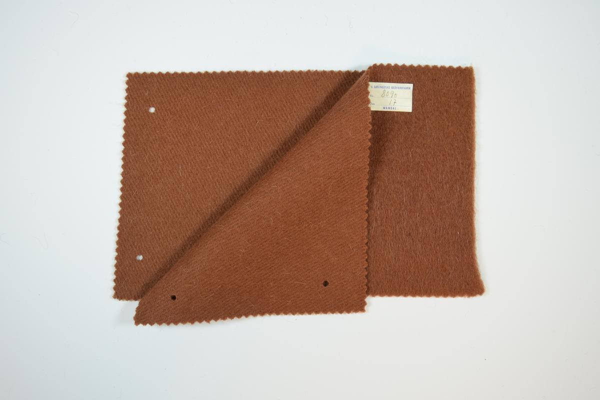 Tre stoffprøver klippet med sikksakk-saks. Middels tykke ensfargede ullstoff . Vevmønsteret kan sees på vranga, men ikke på rettsiden. Kyperbinding/diagonalvevd. Prøvene er brettet slik at formatet blir likt prøvene som finnes i prøvebøker fra Sjølingstad. Alle har to runde hull i margen etter å ha vært/eller skulle bli stiftet til bok eller et hefte. Stoffene er merket med en firkantet papirlapp, limt til stoffet, hvor stoffnummer er trykket i et maskinskrevet skjema.   Stoff nummer.: 8090/15, 809/17, 8090/18.