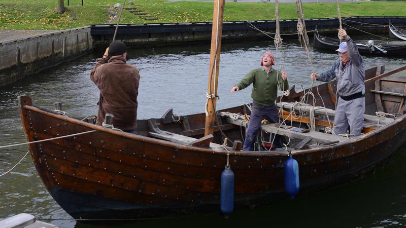 Trebåten Vaaghals, tre personer ombord, mast, foran to blå fendere.