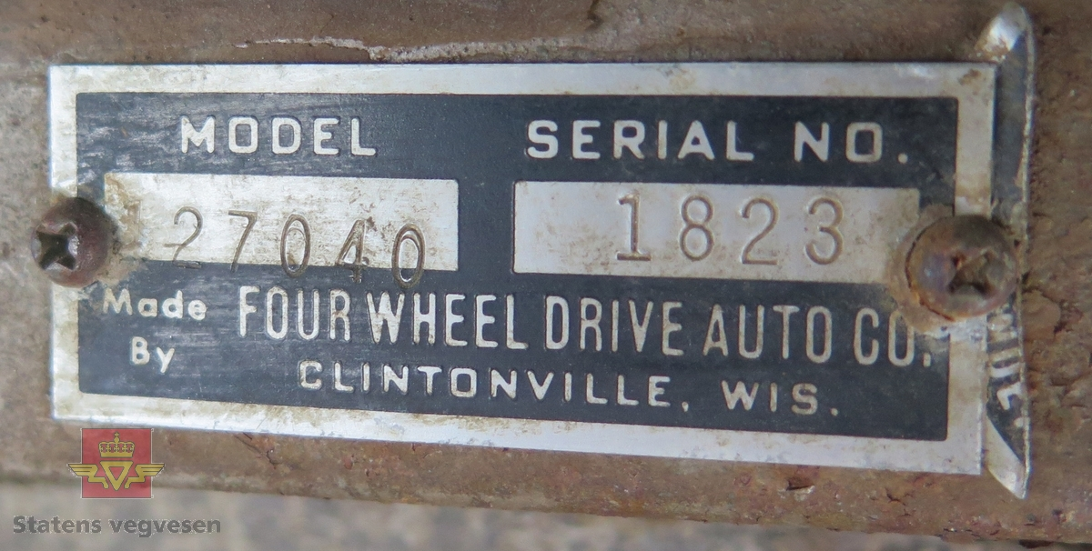 Oransje lastebil med tippsylinder, mangler plan. Bilen har 6 hjul og har bakhjuls-trekk med konstant firehjulstrekk, (merk: FWD). Bilen har et spesielt tippsylinderarrangement der oljekassa fungerer som vogge. Motoren er uoriginal, den er en 6-sylindret rekke motor fra Chevrolet, motorstørrelsen er 292 cui. Fronstykket er hvitt, (trolig byttet). Uten tvil en Chevrolet 292cid rekke 6.