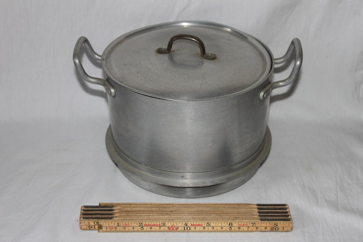 Svagt kupat lock med liten fastnitad tvärgrepe av järn.