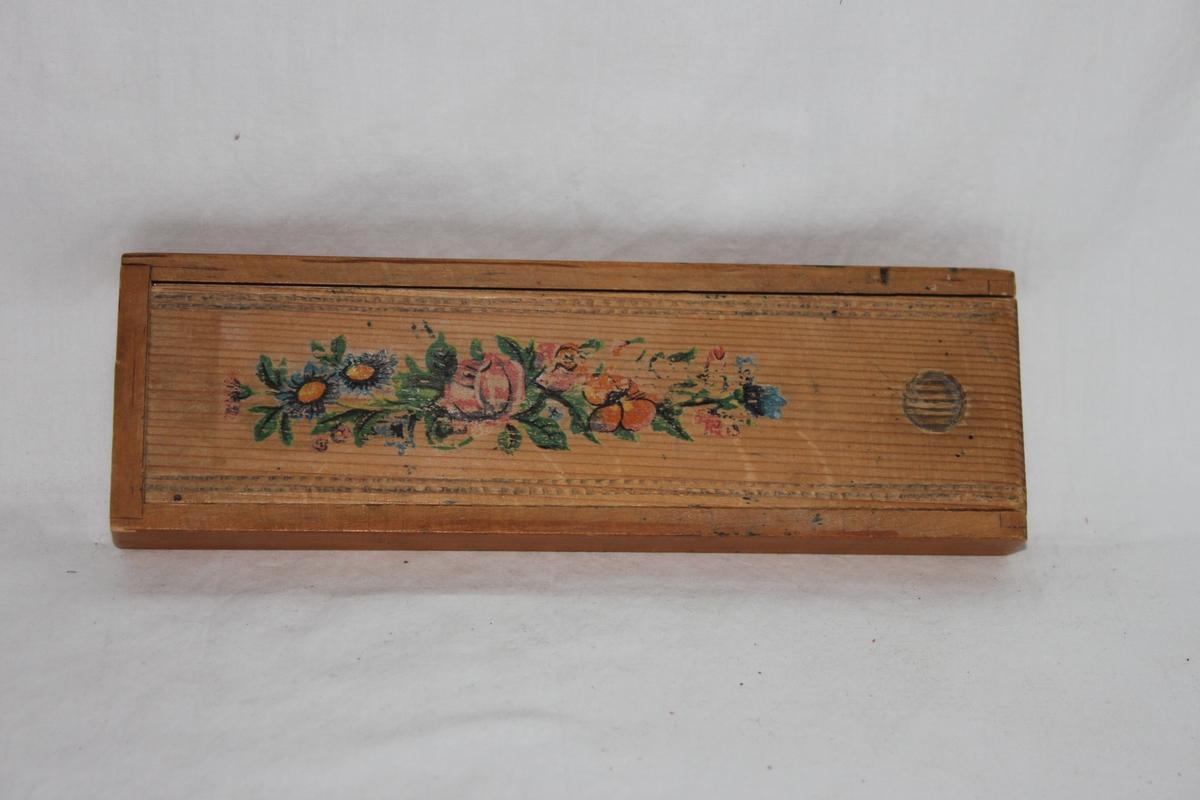 Pennskrin i trä med skjutbart lock, vilket är dekorerat med blommor och blad. Har en rund urgröpning i locket som används vid lockets öppnande. I skrinet finns fyra fack innehållande en äldre bläckpenna, stålpenna, samt en utbytbar stålspets.