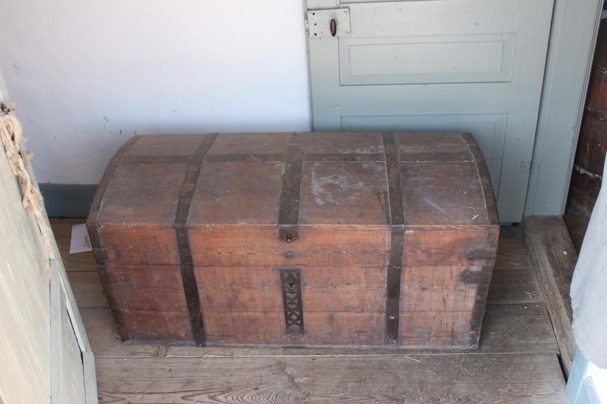 Kista med välvt lock på vilket det finns en längsgående och tre tvärgående band. Locket är fästat med nitade gångjärn på baksidan och öppnas med en knopp av järn. På sidorna sitter ovala järnhandtag. Alla kanter är järnskodda. Nyckelhålsbeslaget har hjärtformat, triangulärt, genombrutet mönster. Utanpåliggande låshus inuti kistan. Inredning med två trälådor i locket. Läddika utan lock på vänster sida.
