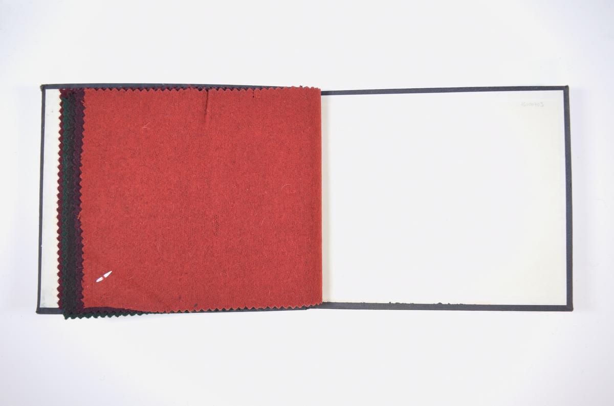 Rektangulær prøvebok med harde permer og fem stoffprøver. Permene er laget av hard kartong og er trukket med sort tynn tekstil. Boken inneholder middels tykke ensfargede stoff. Toskaftbinding, mest synlig på de to første stoffene - de tre siste ser ut til å være noe tovet/valket og er tettere. Verken stoffet eller boken er merket med nummer, slik de fleste andre prøvebøker er (utvisket skrift er missvisende og stemmer ikke).   Ukjent/uten stoffnummer.