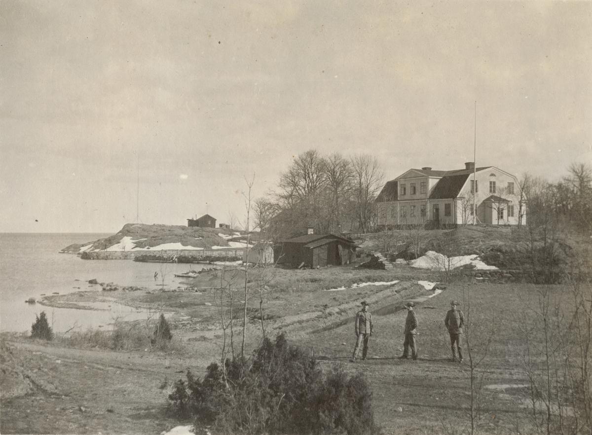 Kustlandskap med trähus och tre soldater.