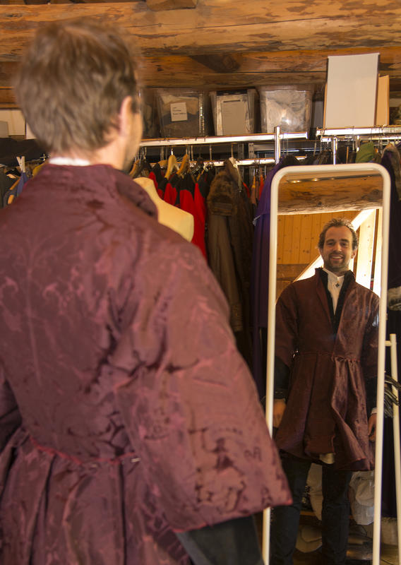 Mann i burgunderrød brokadejakke med store skjørt ser på seg selv i speilet og smiler.