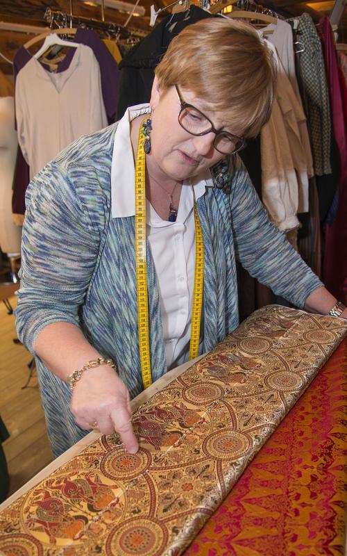 Skredderen viser fram en tøyrull med vakkert rødt og gyllent silkestoff med innfløkt mønster av blant annet arabiske tegn.