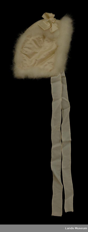 Lys dåpslue med sløyfe på toppen og edderdunskant rundt lua og på sidesømmer.