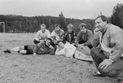 Fotballspillere liggende på fotballbane