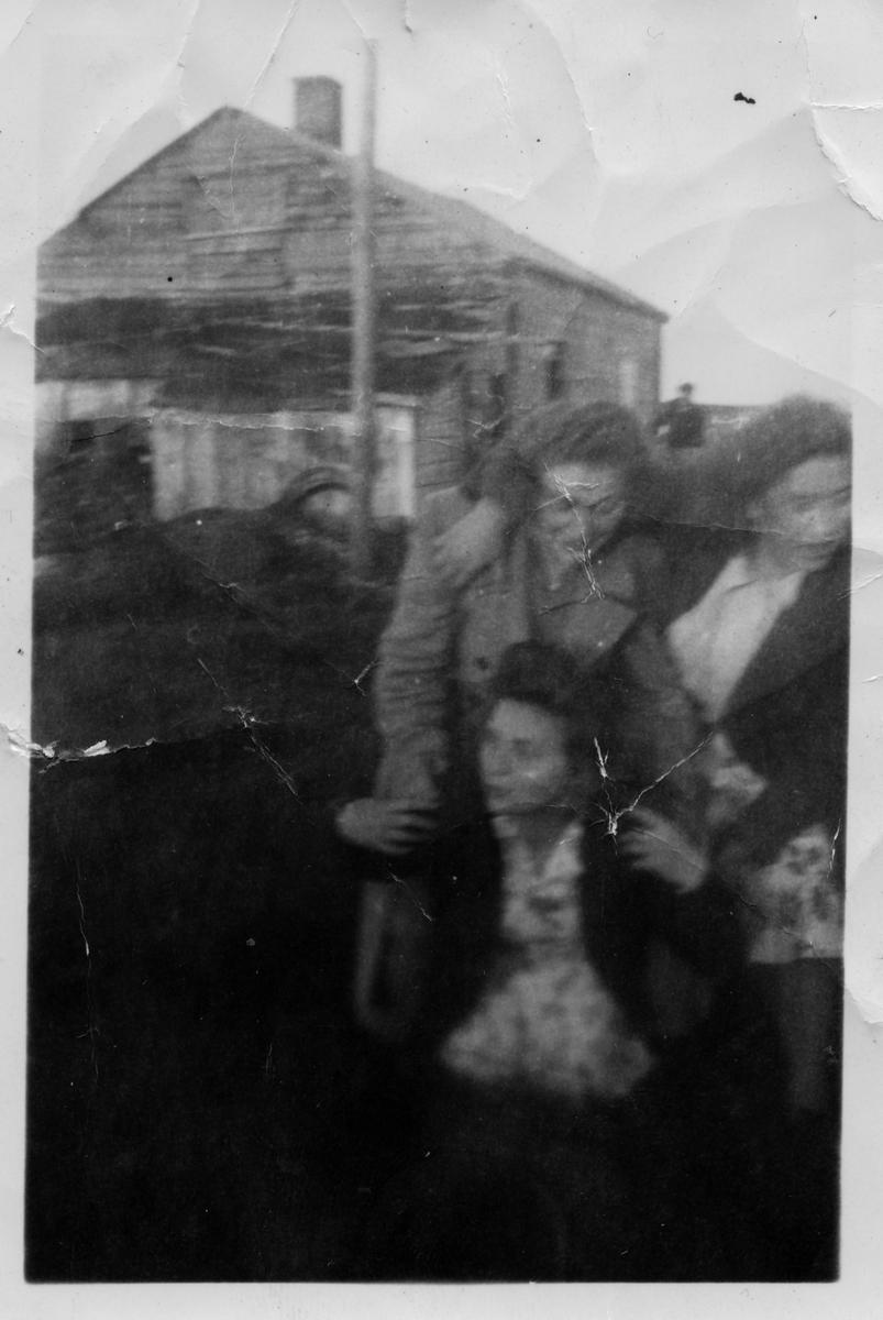 Ruth Kandola og venninner i Golnes i trivelig lag. Den ene blir båret på ryggen. I bakgrunnen ses en mannsskikkelse ved siden av bolighus.