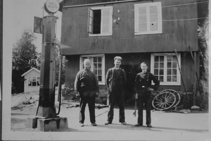 """Gunnar Håkensens første """"butikk"""" med salg av hjemmelaget iskrem, mineralvann og tobakk. Smedene Hans og Håkon Haakensen sammen med lærling/smedgutt i 1930-årene. Bensinpumpa ble satt opp i 1928."""