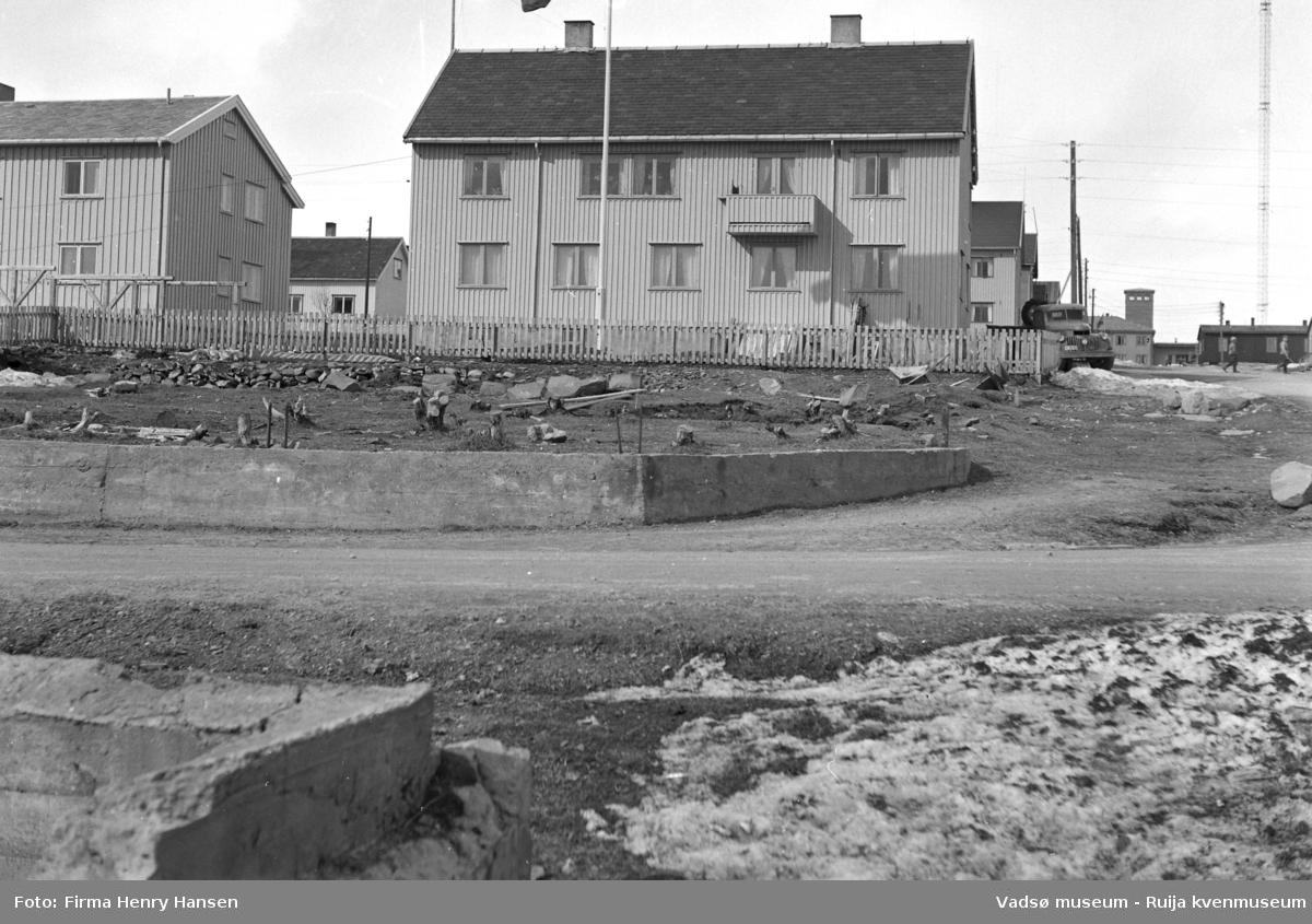 Vadsøbilder 1952 Alrik Basmas bygg. Bildet er tatt fra syd mot nord. I forkant av bildet Hvistendalsgate med deler av en grunnmur syd for veien og deler av en mur med forskaling rett nord for veien. Midt i bildet et stort gjenreisningshus i to etasjer med skifertak. I andre etasje en luftebalkong. Til høyre for bygningen står en lastbil parkert.  Innafor gjerdet som går rundt bygningen en flaggstang og tørkestativ. Til venstre innafor gjerdet ser vi deler av et annet gjenreisningshus også i to etasjer med skifertak. Til høyre i bildet går Skolegata opp mot brannstasjonen, og vi ser gjenreisningshus langs Skolegata. Øverst i bildet helt til høyre skimtes den ene av radiomastene.