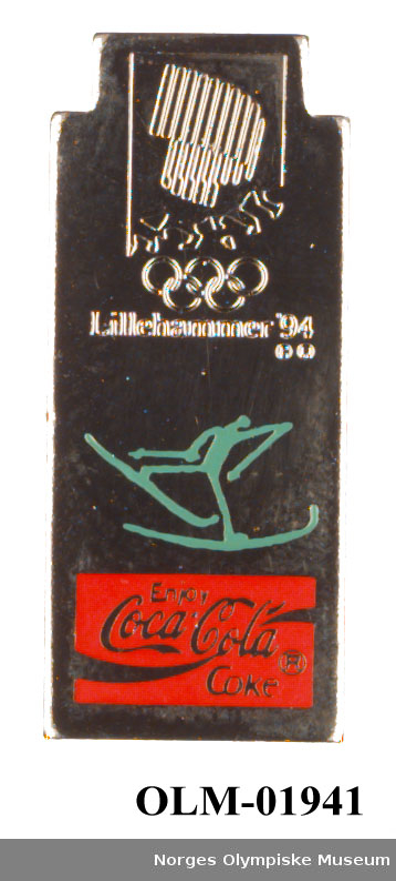 Rektangulært smalt stående merke med emblemet for Lillehammer '94 øverst, piktogram for langrenn i midten og logo for Coca Cola på rød bakgrunn nederst.