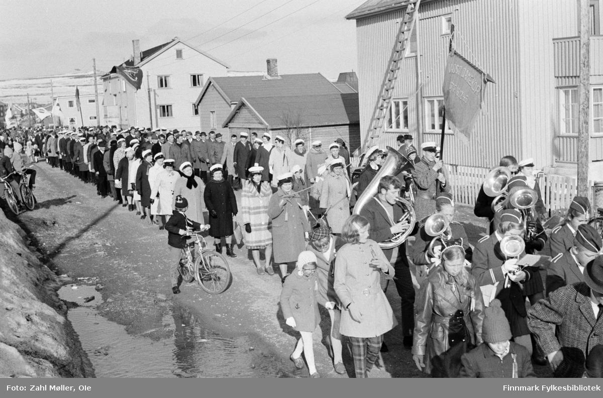 Vadsø 17.5.1969. Fotoserie av Vadsø-fotografen Ole Zahl-Mölö. Nærbilde av muskkorpset med sangforeningens medlemmer hakk i hel. Muligens Sangen og Musikkens dag i Vadsø. Legg merke til barna som følger med paraden!