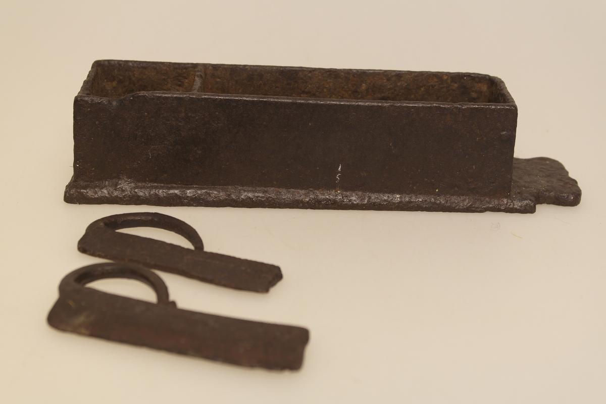 Fyrtøy bestående av skrin (a) og to ildjern (b-c).  A) Skrin i støpt jern. To rom; ett for knusk og ett for flint og ildjern. B) To like ildjern i støpt jern. Riflet overflate og krumt håndtak.