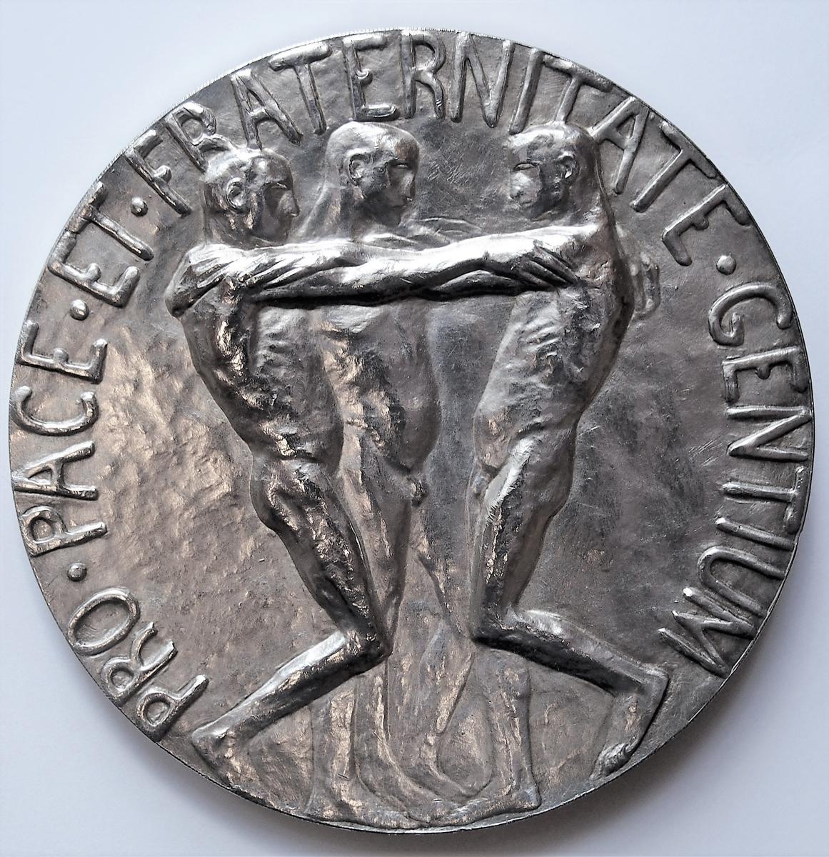 Medalje med motiv på avers: portrett av Alfred Nobel i profil, omgitt av innskriften ALFR.NOBEL.NAT.MDCCCXXXIII.OB.MDCCCXCVI  Til høyre står MODEL.G.VIGELAND   Motiv på revers: tre nakne menn som holder hverandre om skuldrene, omgitt av innskriften PRO.PACE.ET.FRATERNITATE.GENTIUM