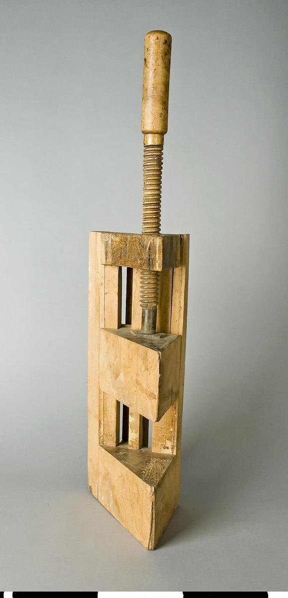 Stötlåda av bok. Stötlådan består av ett flertal trästycken som med skruvar och lim är ihopsatta till en tresidig klotsliknande låda. I den ena änden finns en träspindel med vars hjälp man flyttar den rörliga delen av stötlådan. I stötlådan spänns arbetsstycket fast för hyvling av ändträet. Stötlådan monteras i hyvelbänk vid arbetet. Längden är beräknad inklusive spindelns handtag.