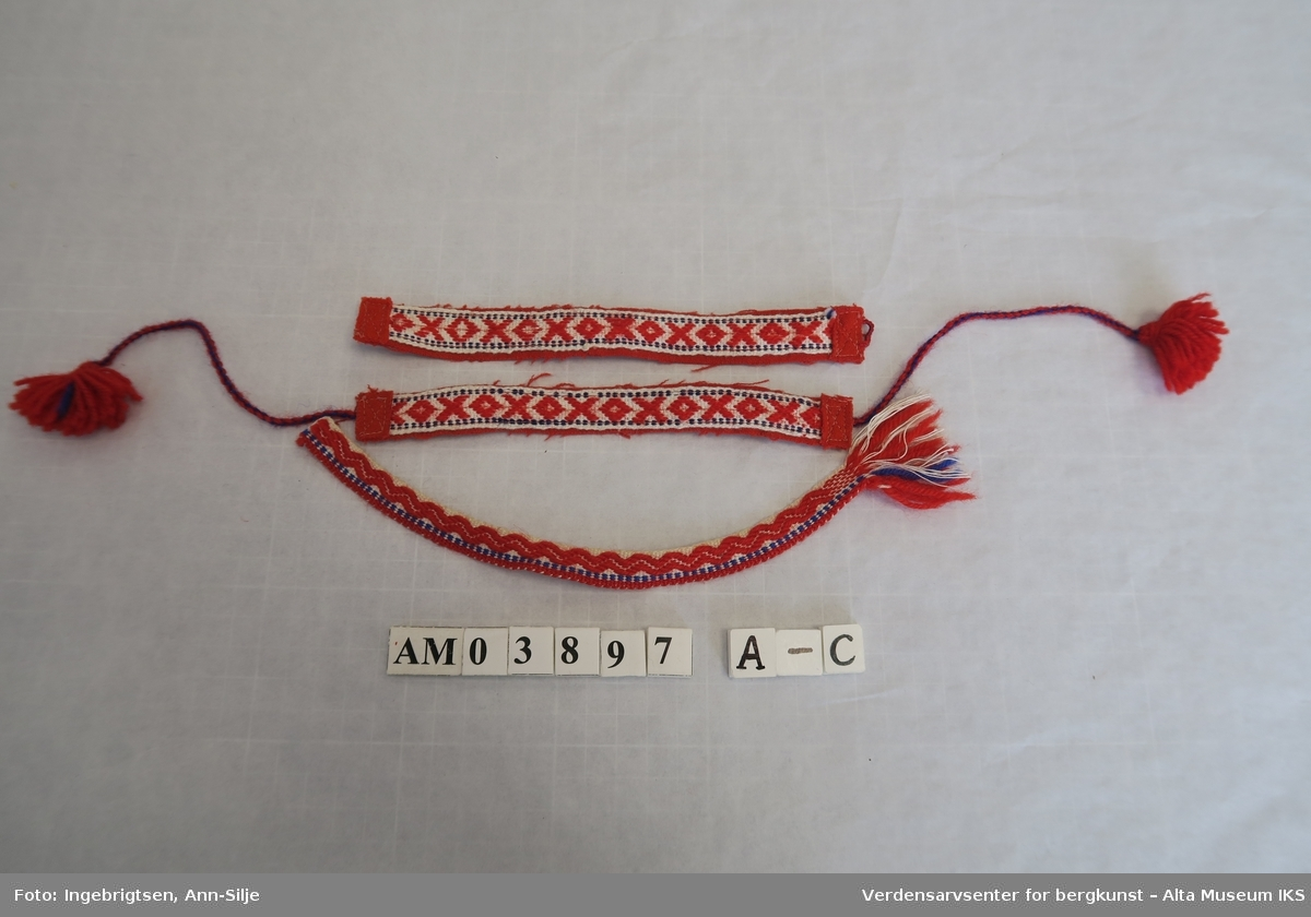Vevde dukkebelter. De er mest sannsynlig laget av overskuddsbånd til beltekant eller skallebånd. Mønstrene på båndene ble brukt flere steder i Finnmark.