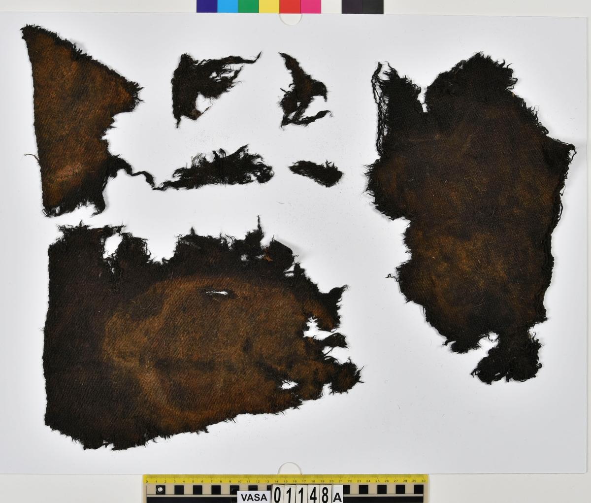 Textilier. 12 stycken textilfragment med fyndnummer 01148a-f. Fnr 01148a består av 7 fragment av ull vävda i 2/1-kypert. Några av fragmenten har vissa bevarade originalkanter. Fnr 01148b består av ett fragment av ull vävt i tuskaft. Fnr 01148c består av ett fragment av ull vävt i tuskaft. Fnr 01148d består av ett filtat fragment. Fnr 01148e består av ett fragment av ull vävt i tuskaft. Fnr 01148f består av ett fragment av ull vävt i tuskaft. Fragmentet ser ut att ha varit valkat.
