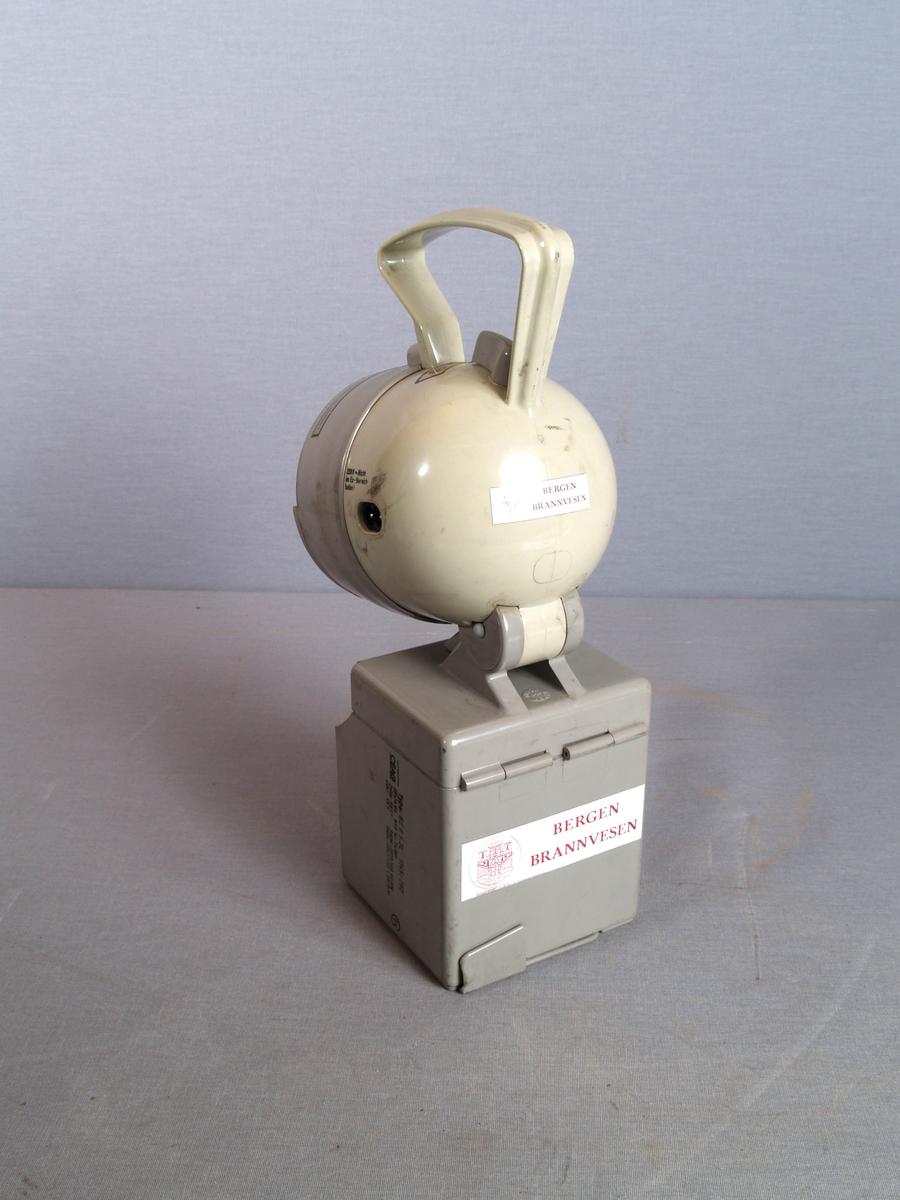 Lyskaster/gasslykt. Håndlykt med bevegelig hode med pære, håndtak og bryter. Sirkulært lykteglass i plastomramming. Utenpå et halvsirkelformet spor for ekstra lykteglass. Basis er en kube med lomme for lykteglass i front. Lyktehodet er festet på toppen av kuben.