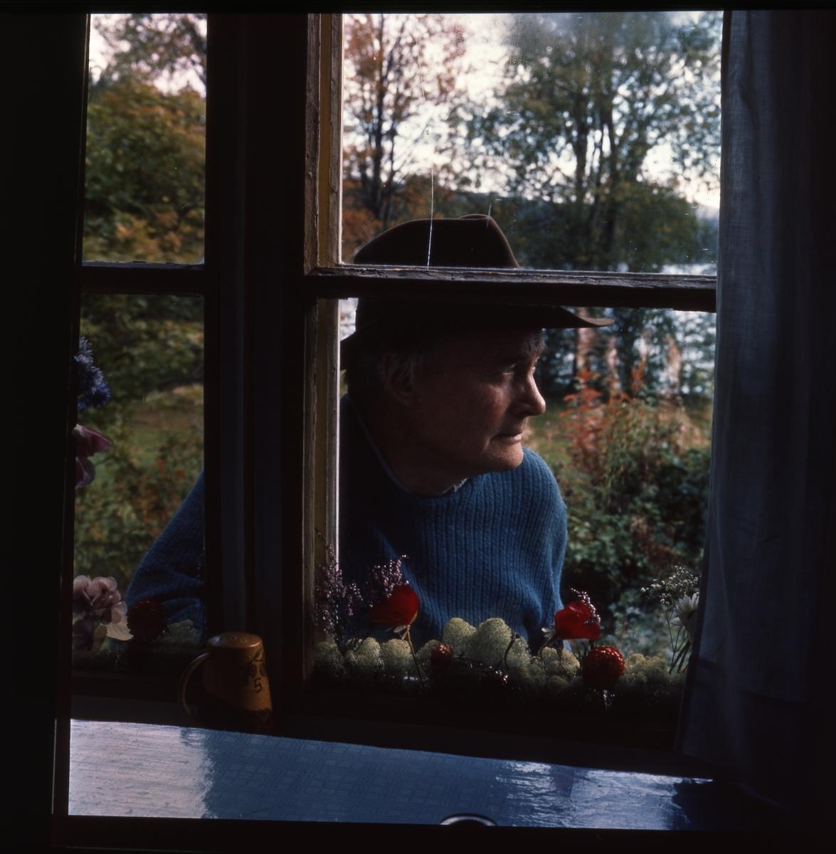 Utanför ett av de spröjsade fönstren på skrivarstugan står Albert Viksten iklädd hatt. Naturen har höstfäger.