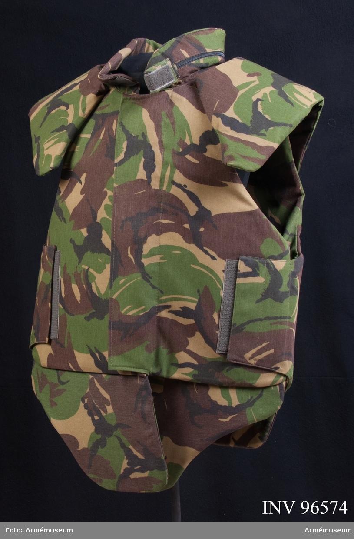 "Kroppsskyddsväst i Woodland-camouflage. På etiketten i skyddsvästen står följande: ""LBA Wahler GmbH. D-8355 Hengerberg. Schwanenkirschnerstr. 20.Body Armour -90. Musterweste Typ1""."