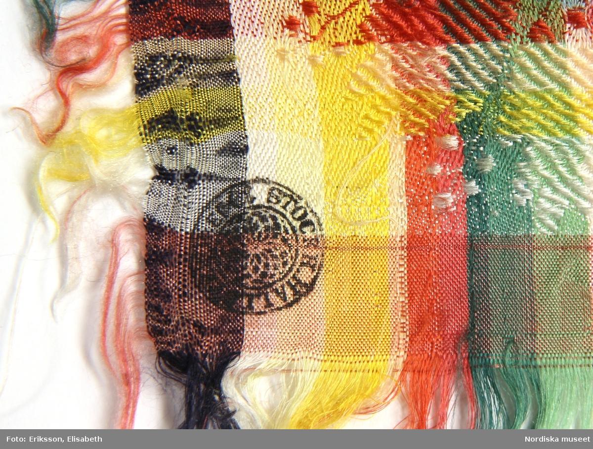 Kvadratiskt halskläde i siden med jacquardvävt mönster, mittspegeln svart och rosa med likadant lansettbladmönster  över ytan, kantbården är på 2  sidor randig i rosa,  gult, vitt,orangeröt t och grönt med  palmettlikt mönster, på de andra 2 sidorna är botten istället svart  med mönstret i  samma färger för övrigt. På alla sidor kort upprispad frans . I ena hörnet en rund röd stämpel med texten: Stockh. Hallstemp. 1843. I fint skick. Klädet  har ett av de vanligaste mönstren i Hälsingematerialet. Se t.ex.  kläde 155879 från Alfta och 111 491 från ovanåker. Alla har hallstämplar från 1830-40-talen. /Berit Eldvik 2011-11-14