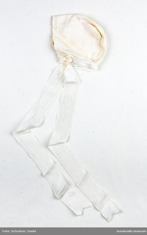En dophätta i siden med knypplad spetskant. Hättan knyts med två långa sidenband som fästs i kanten med rosetter av samma tyg.
