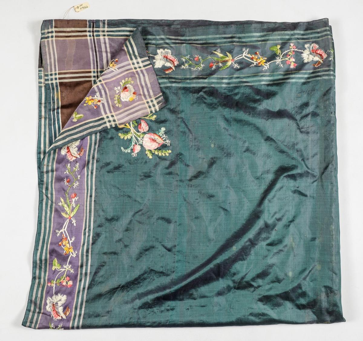 Tørkle i blå-grønn silke. Striper i brunt, grønt og kvitt langs to sider, og dei to andre sidene er stripa i fiolett, grønt og kvitt. broderte blomstermotiv i snippen.  To-preikeplagg.