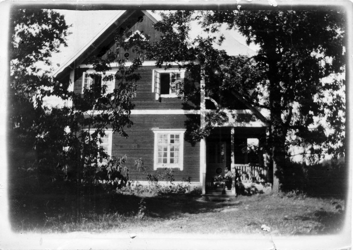 John Bauer sitter på trappan till sitt hus Björkudden utanför Gränna.