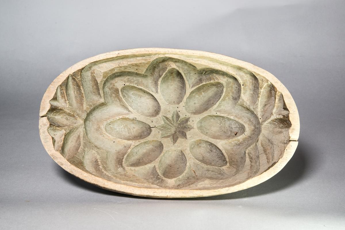 Grötform, oval, av trä, enligt äldre kataloglapp av asp. Invändigt handskuret blom- och stjärnmönster i djup relief. Utsidan slät.