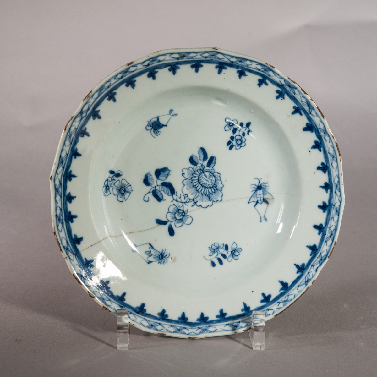 Tallrik av porslin med blå dekor. I spegelns mitt blommor och insekter. Bård runt brättet. Även på undersidan dekor av blommor.