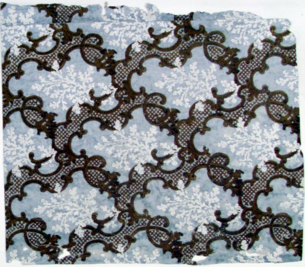 Rut-/medaljongmönster uppbyggt av träimiterande rocailler i två bruna nyanser. Varje mönsterdel är dekorerad med en snöflinge-liknande vit blomma. Bakgrunden utgörs av en ljusgrå limfärgsbotten.
