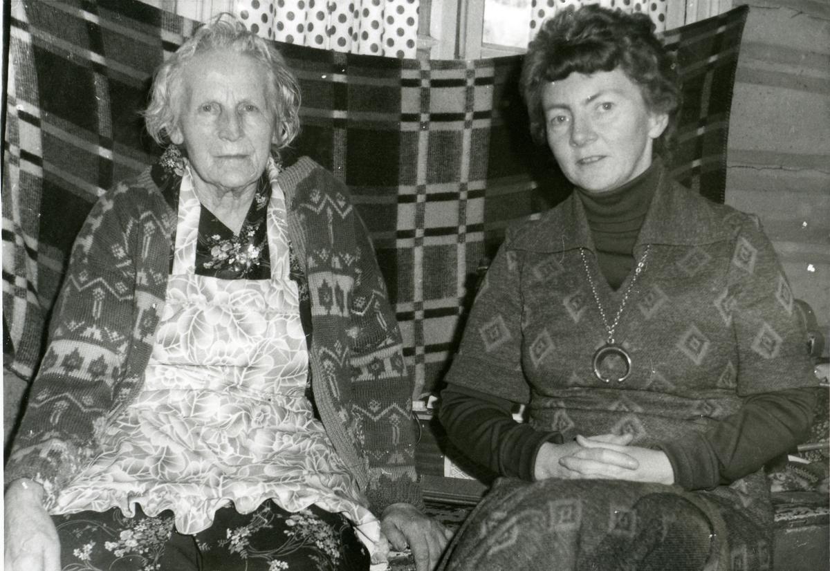 To kvinner sitter foran et et pledd som er oppspent foran et vindu.