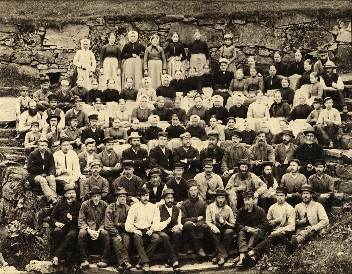 Gruppeportrett av arbeidarane ved Salhus Tricotagefabrik utanfor Bergen, i 1893. Disponent Phillip Christian Clausen og son hans Emil Clausen i midten av biletet.