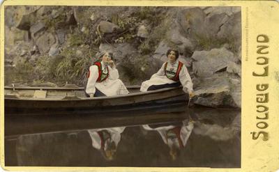 Kolorert fotografi av to kvinner med drakt i pram. 1908.