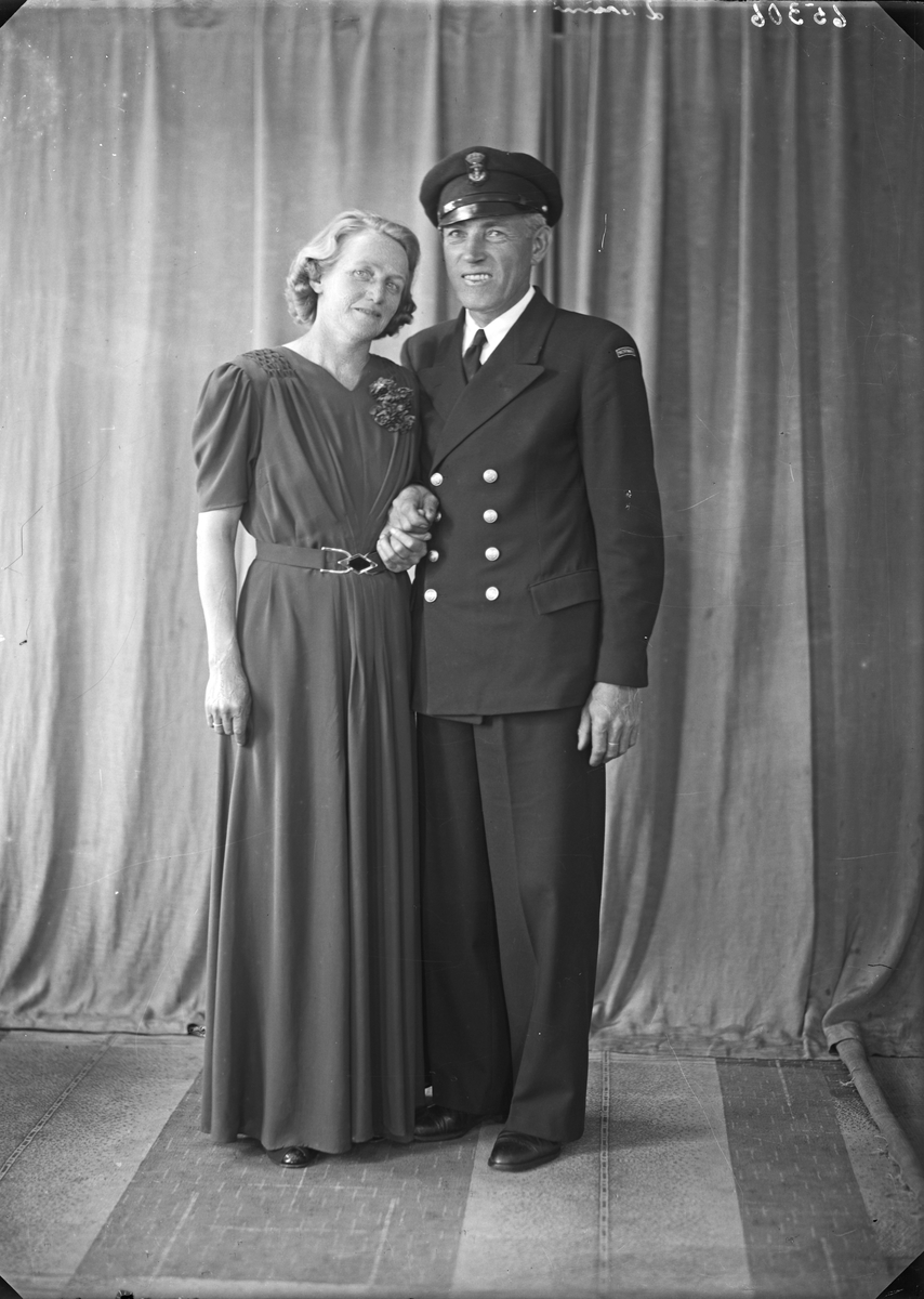 Gruppebilde. Familiegruppe på to. En kvinne og en mann i uniform. Bestillt av Vilh. Larsen.