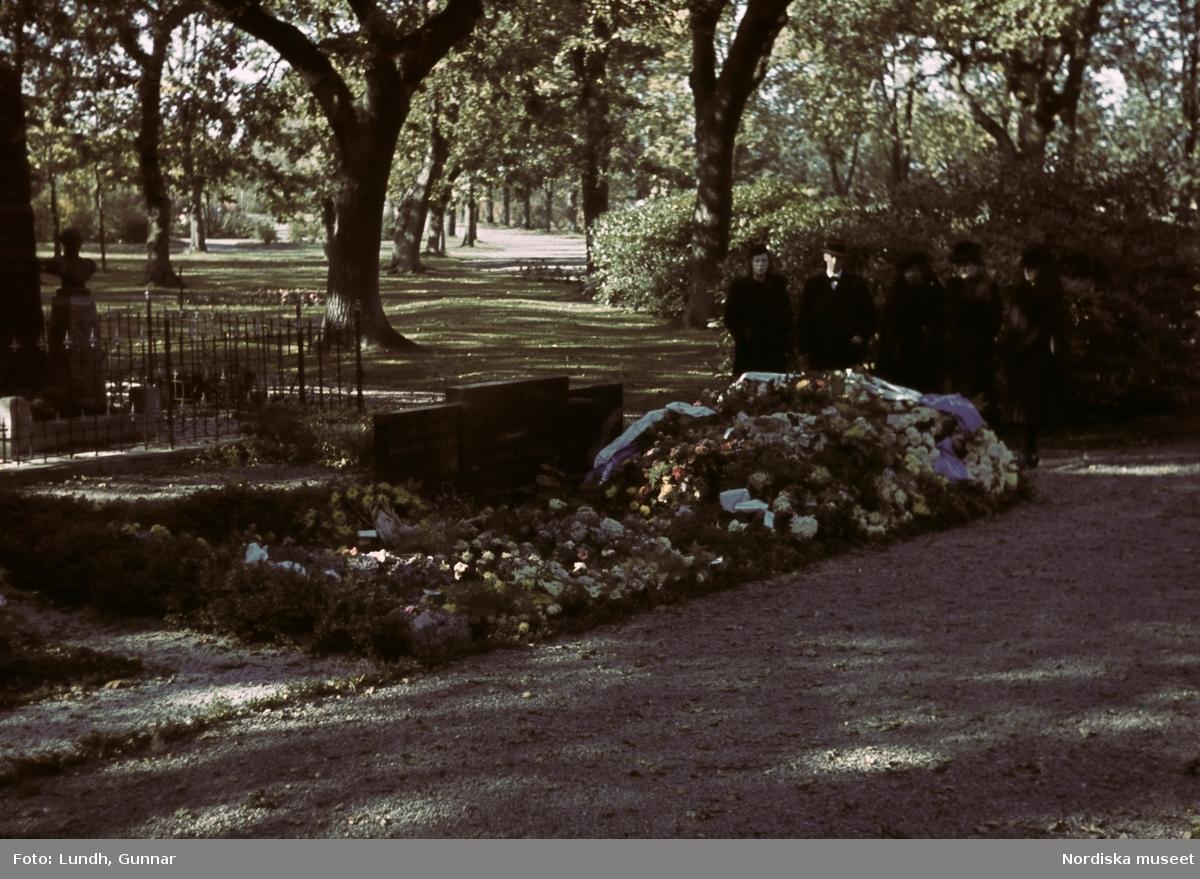 En gravplats med blommor och kistdekorationer. I bakgrunden ett sällskap begravningsklädda, fyra kvinoor och en man.
