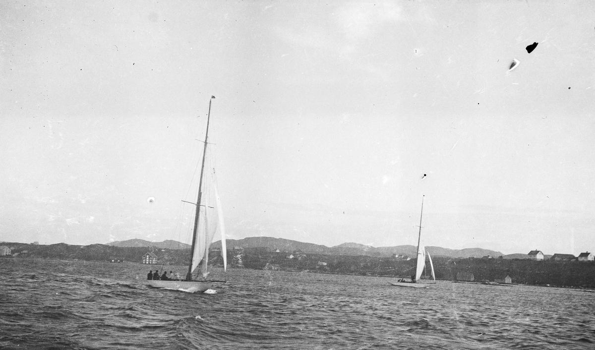 Oversiktbilde. To mindre seilbåter med passasjerer ombord under fart midtfjords. Bebyggelse i bakgrunnen. Hverdagsfoto.