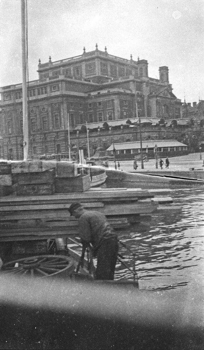 Sommer. Et skip ligger forkant. En mann jobber med tau. Trelast ligger på tvers på skipet. Brei kaiområde. I bakgrunnen sees en større bygning/slott. Hverdagsbilde.