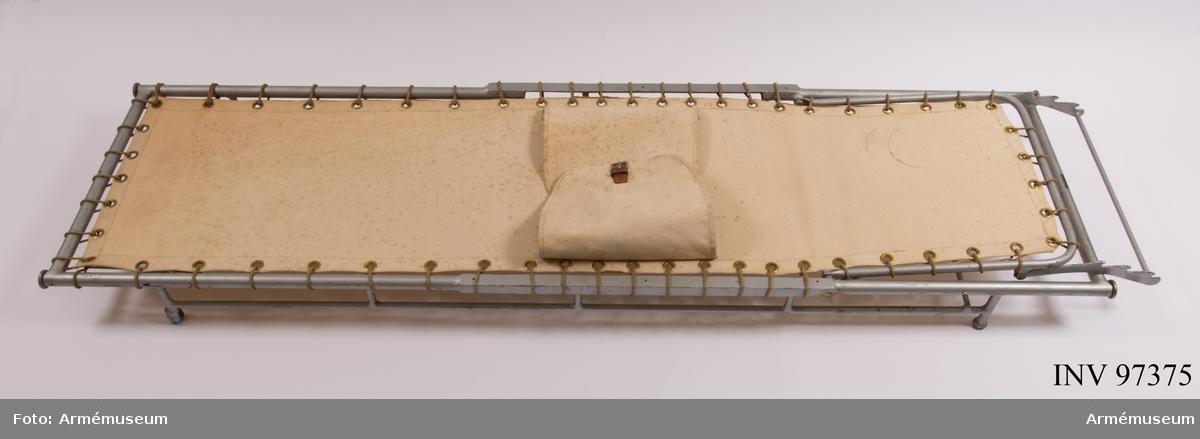 Bår i textil med metallram. Tyget har många fläckar. På bårens undersida har någon ritat en liten streckgubbe.