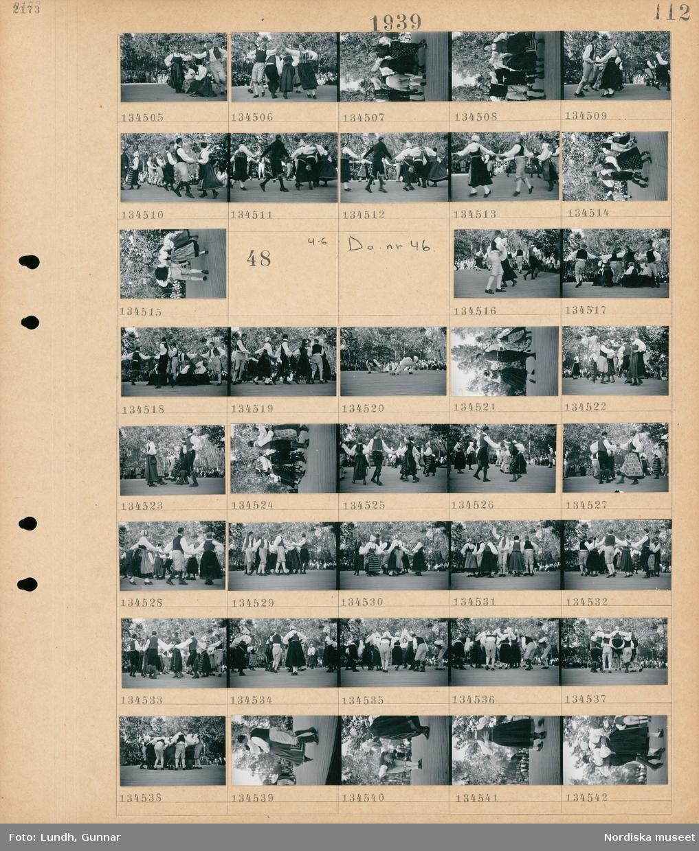 Motiv: Skansen; Kvinnor och män i folkdräkt dansar på en dansbana inför en publik.  Motiv: Skansen; Kvinnor och män i folkdräkt dansar på en dansbana inför en publik.