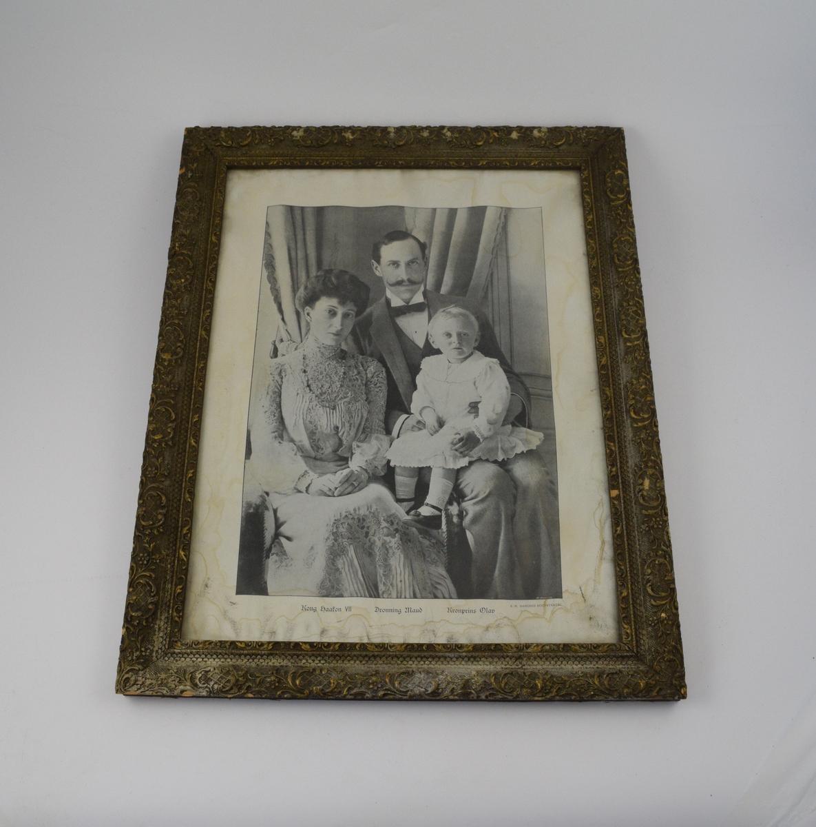Ung mann sittende med et barn på fanget. En kvinne sitter ved hans høyre side, litt foran ham. Draperinger like bak dem, trolig forran et vindu. Personene på bildet er kong Haakon VIII, dronning Maud og kronprins Olav.