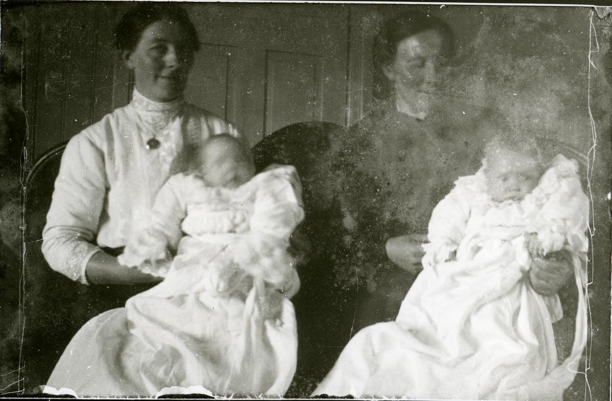 To kvinner sit med kvart sitt barn på fanget.